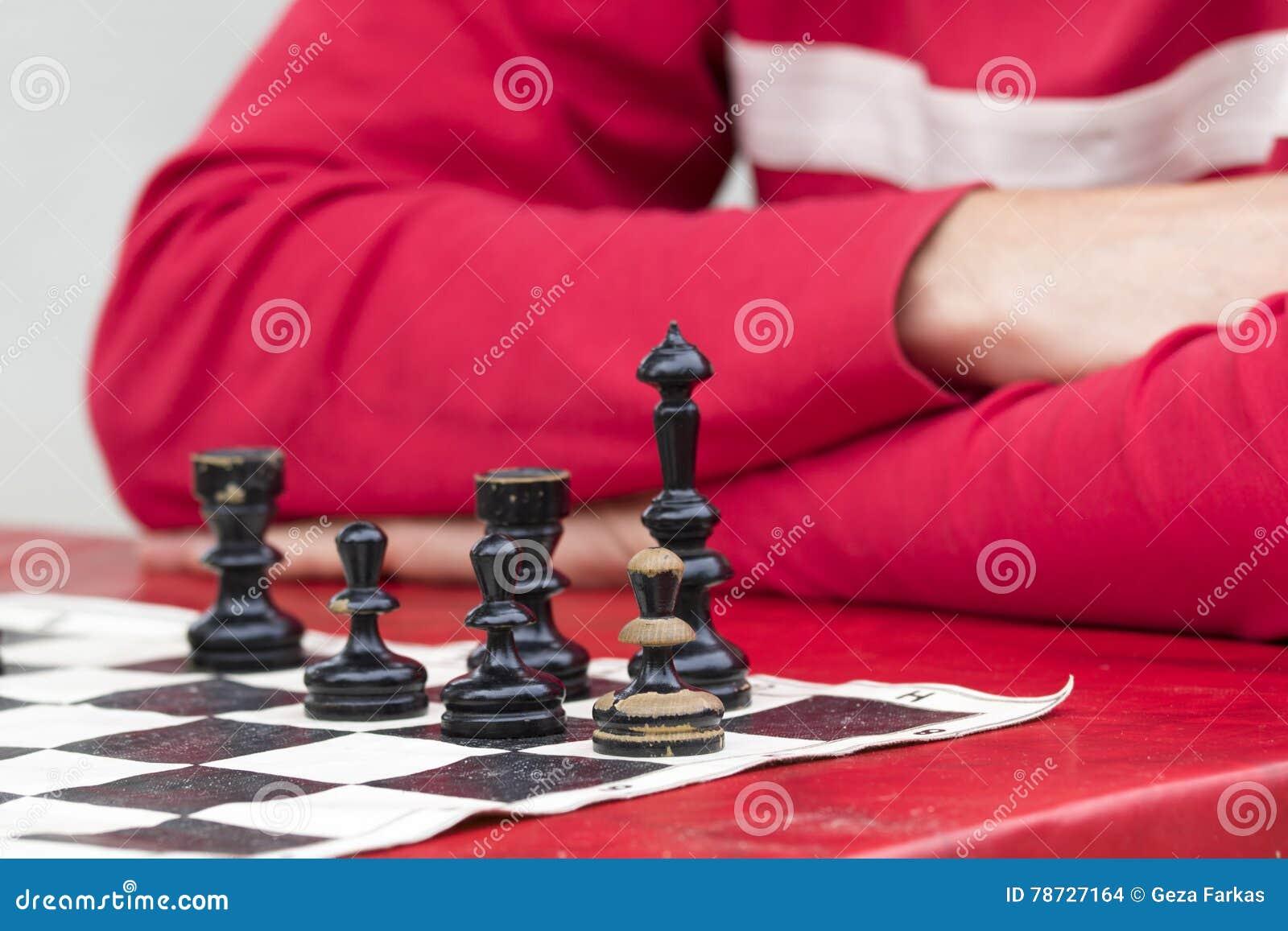 Man i rött spela schack i gammal schackbräde