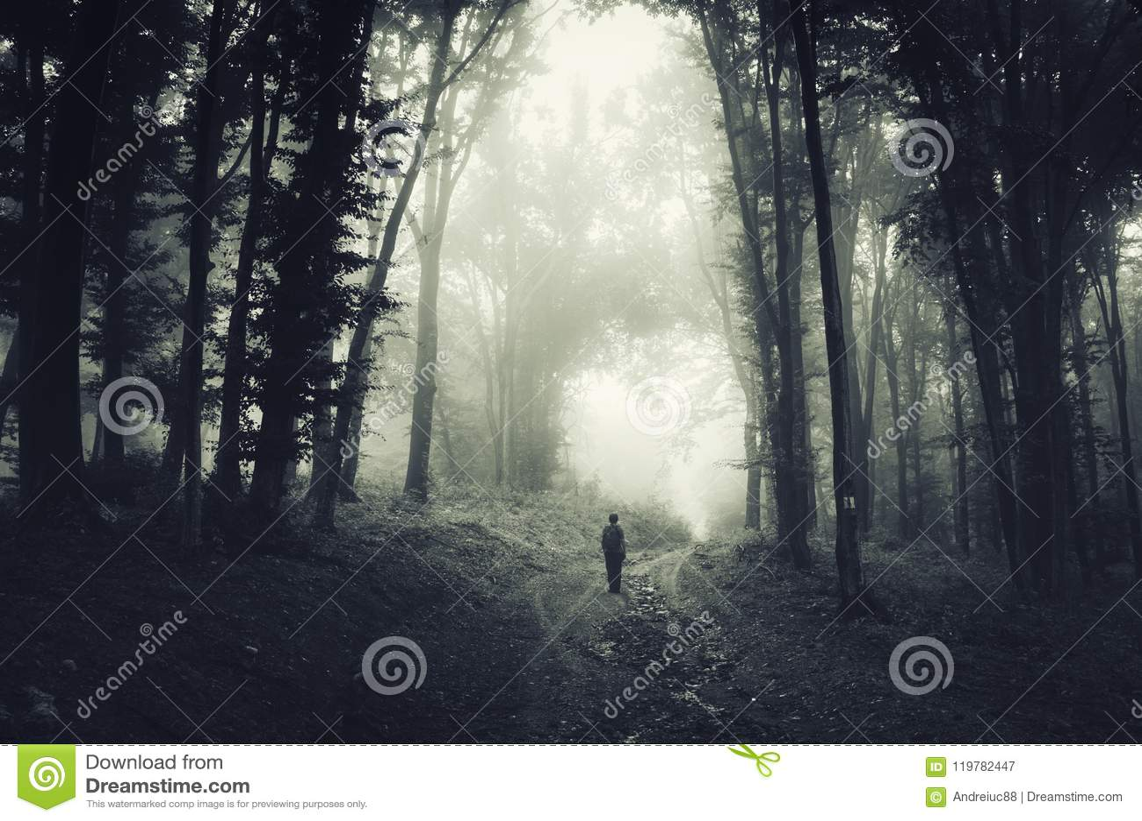 Man i spöklik mörk skog med dimma på allhelgonaafton