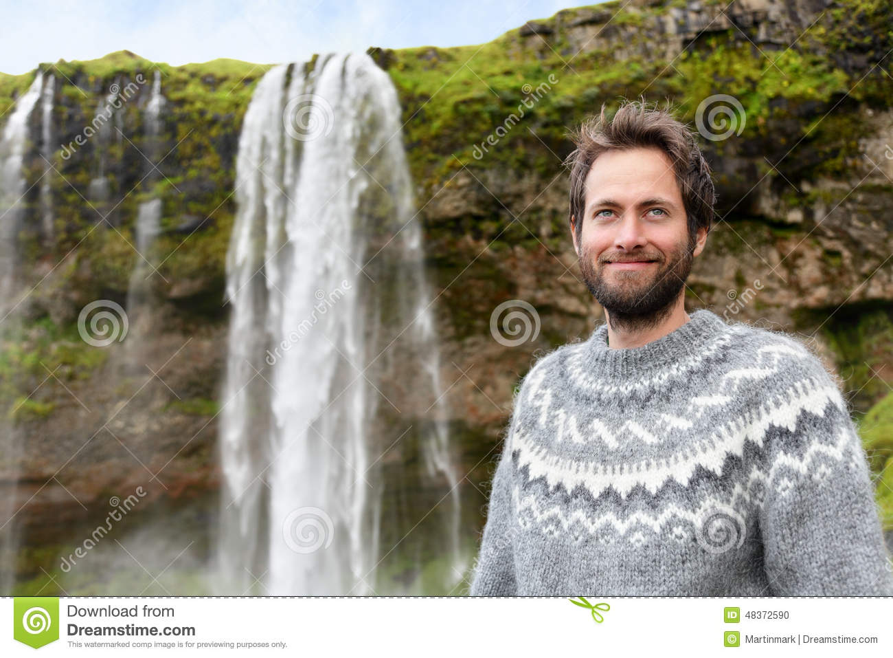 man in icelandic sweater by waterfall on iceland stock photo