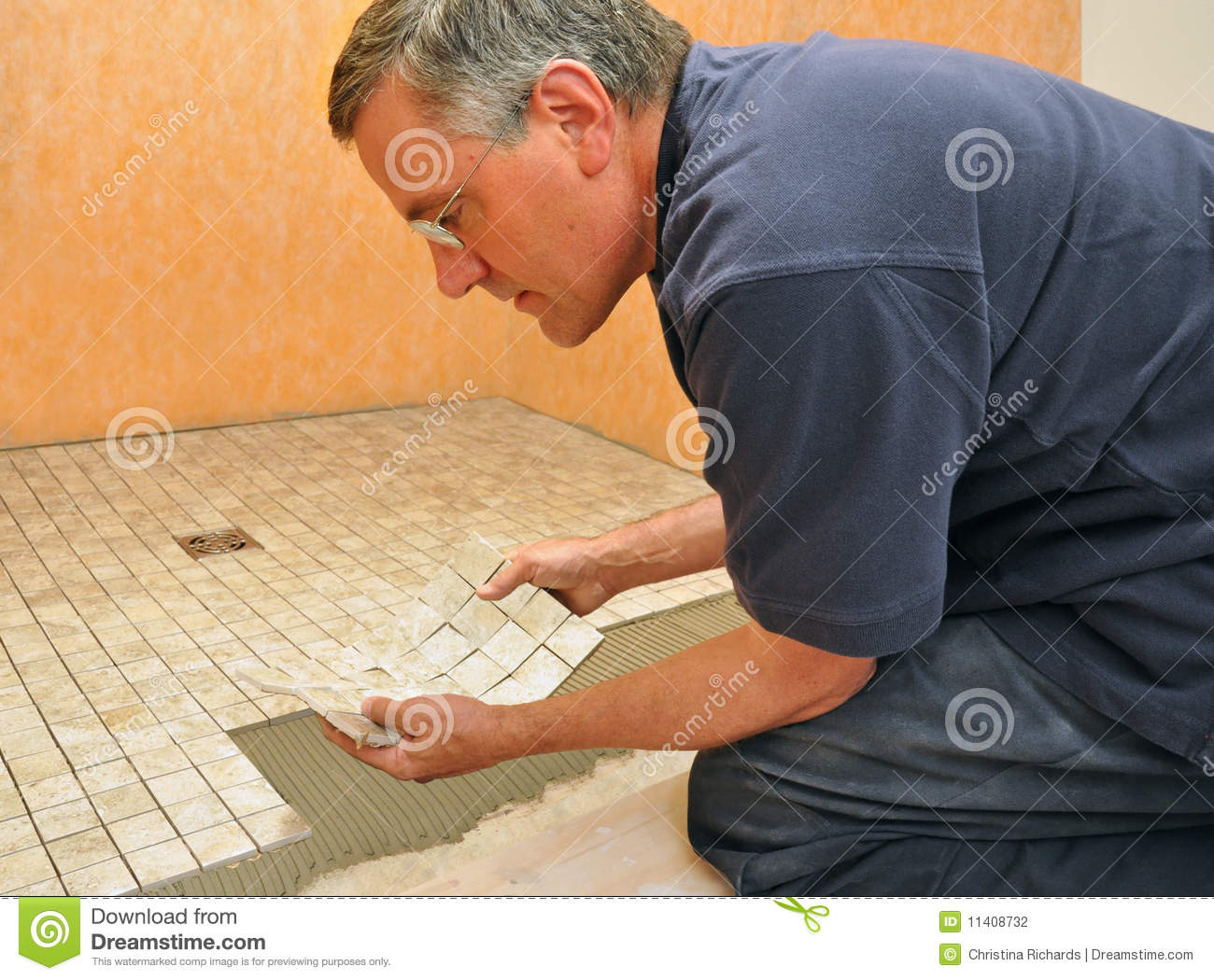 Man installing ceramic tile in bathroom stock photo image of man installing ceramic tile in bathroom dailygadgetfo Gallery