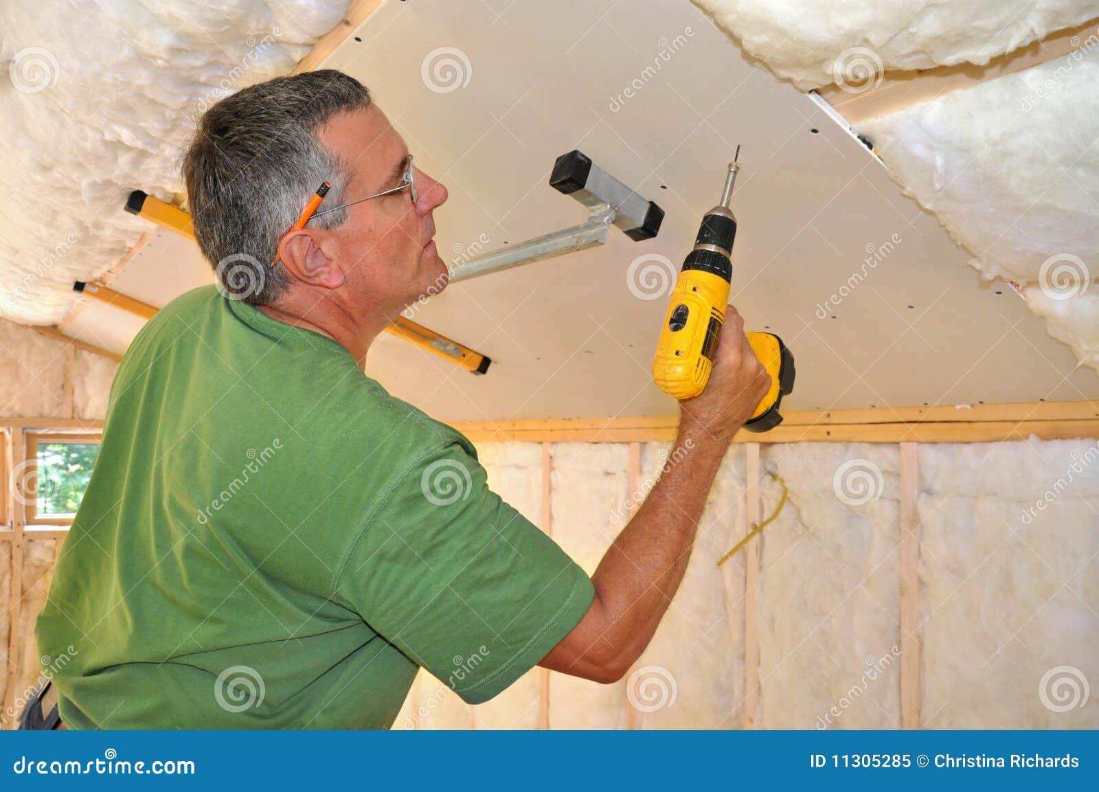 Man installing drywall on ceiling