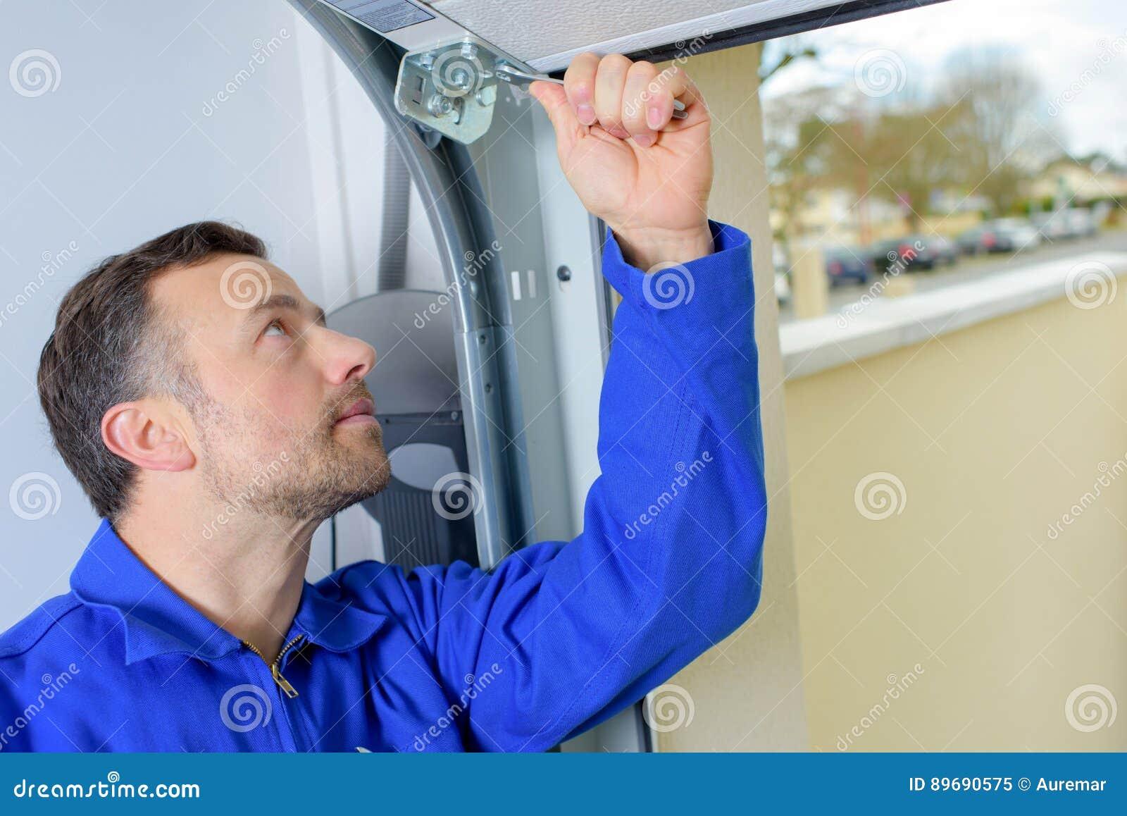 Man installing garage door stock image image of repair for Garage man door