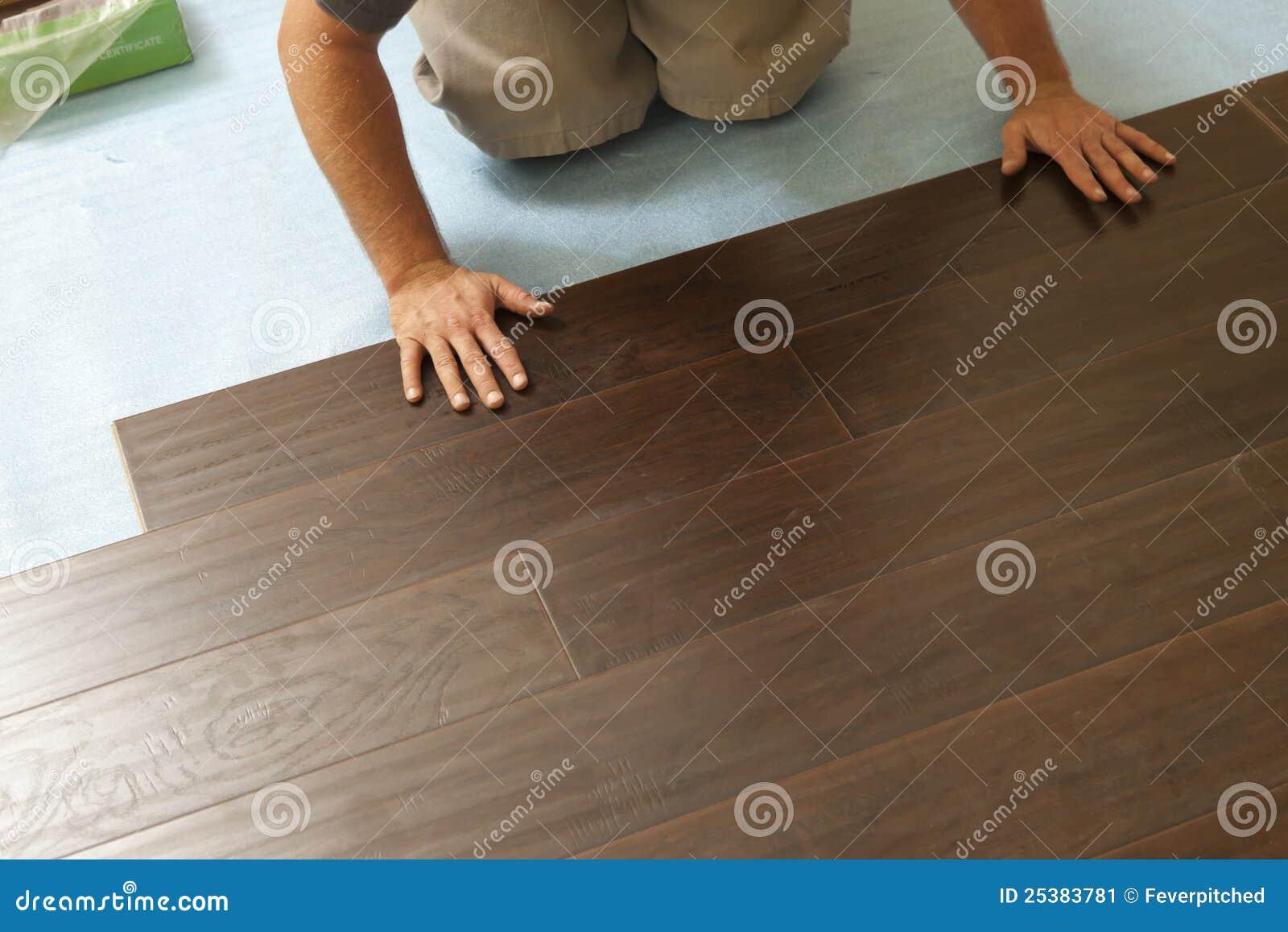 Man installing new laminate wood flooring stock image for Laying laminate flooring