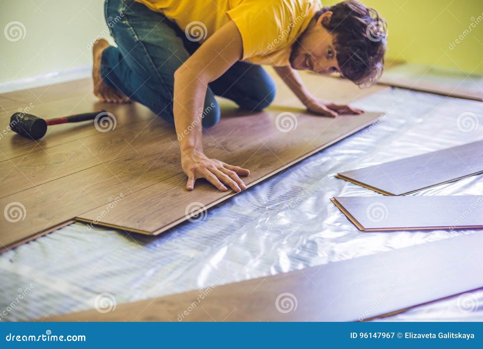 Man installing new wooden laminate flooring. infrared floor heat