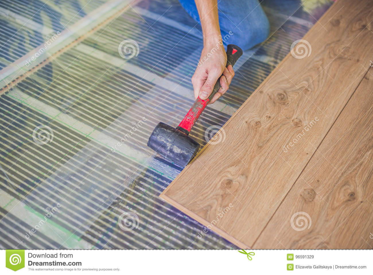 Man installing new wooden laminate flooring. infrared floor heating system under laminate floor