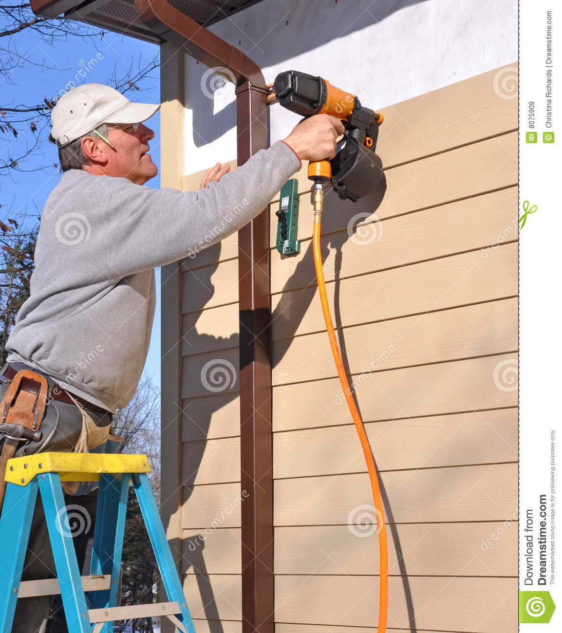 Man Installing Siding With Nail Gun Royalty Free Stock
