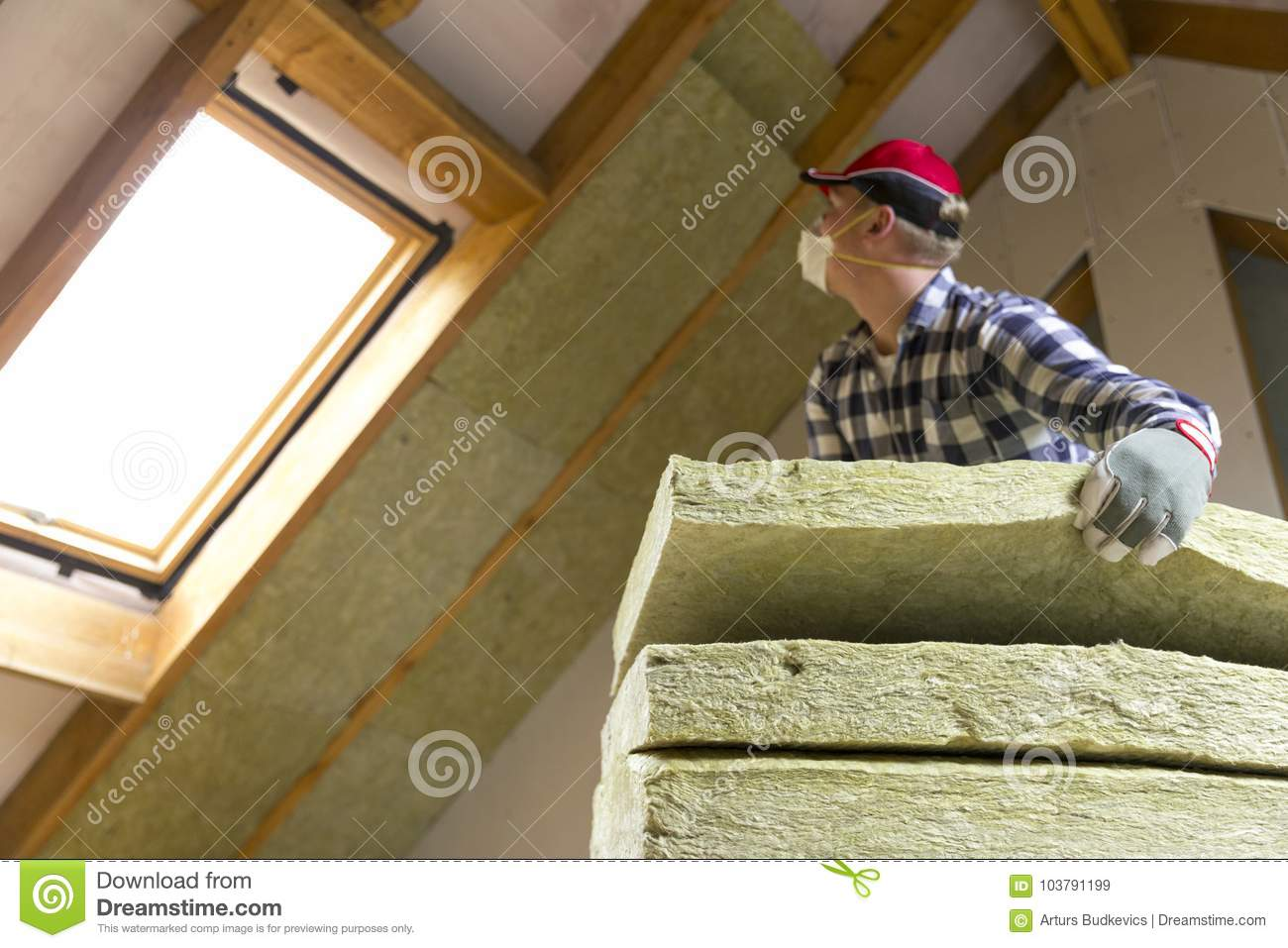 Man installing thermal roof insulation layer using for Mineral wool installation