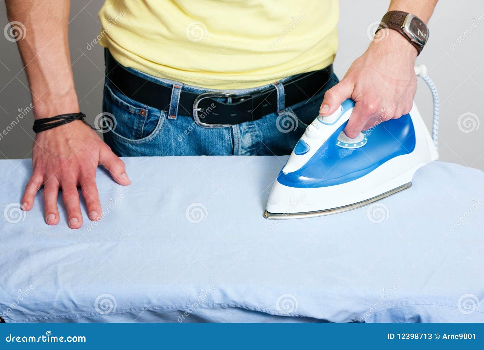 man ironing a shirt stock photos