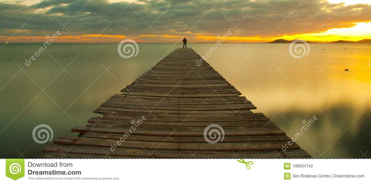 Man on jetty at sunset