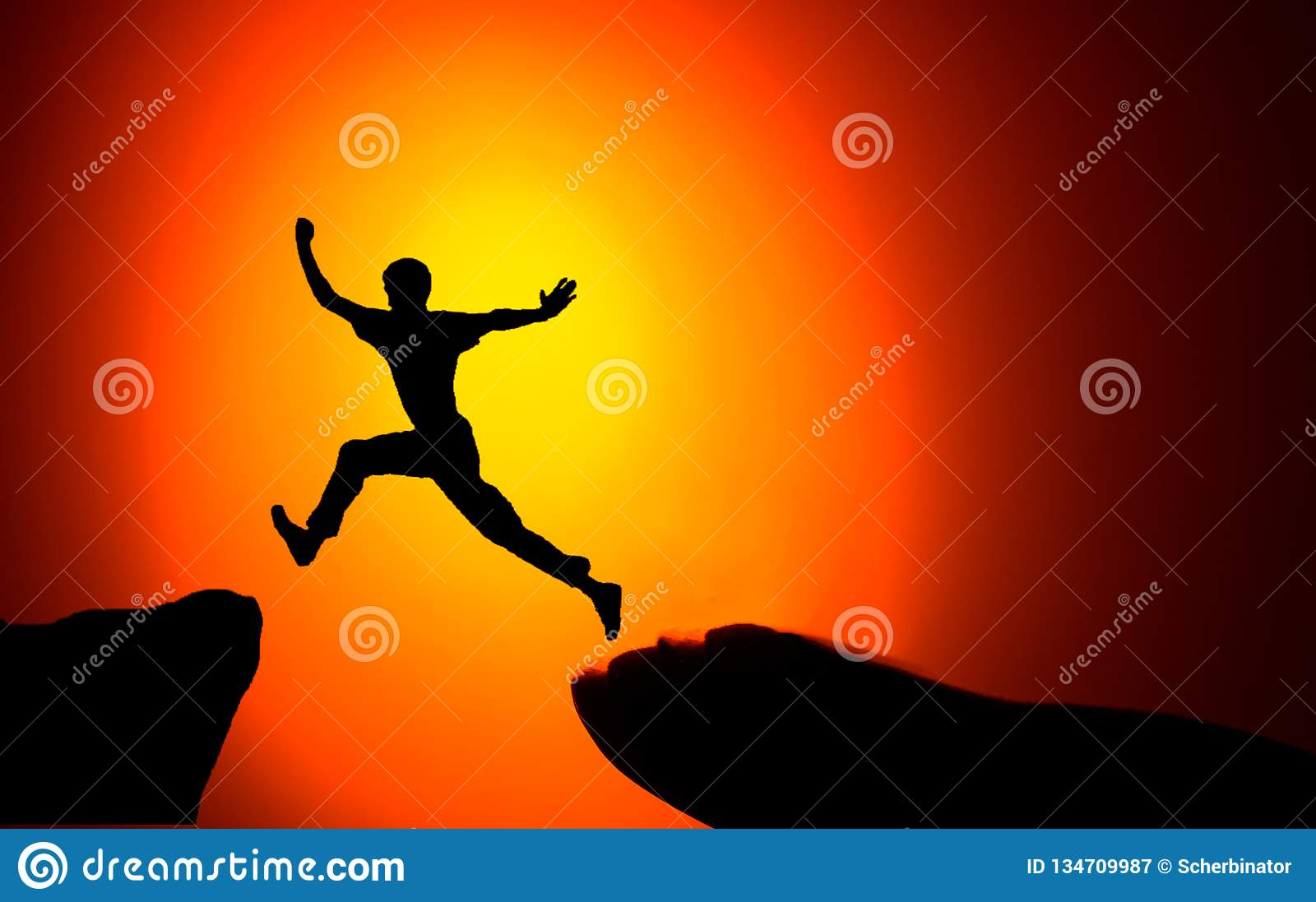 Man jumping across the gap from one rock to cling to the other. Man jumping over rocks with gap on sunset fiery background.