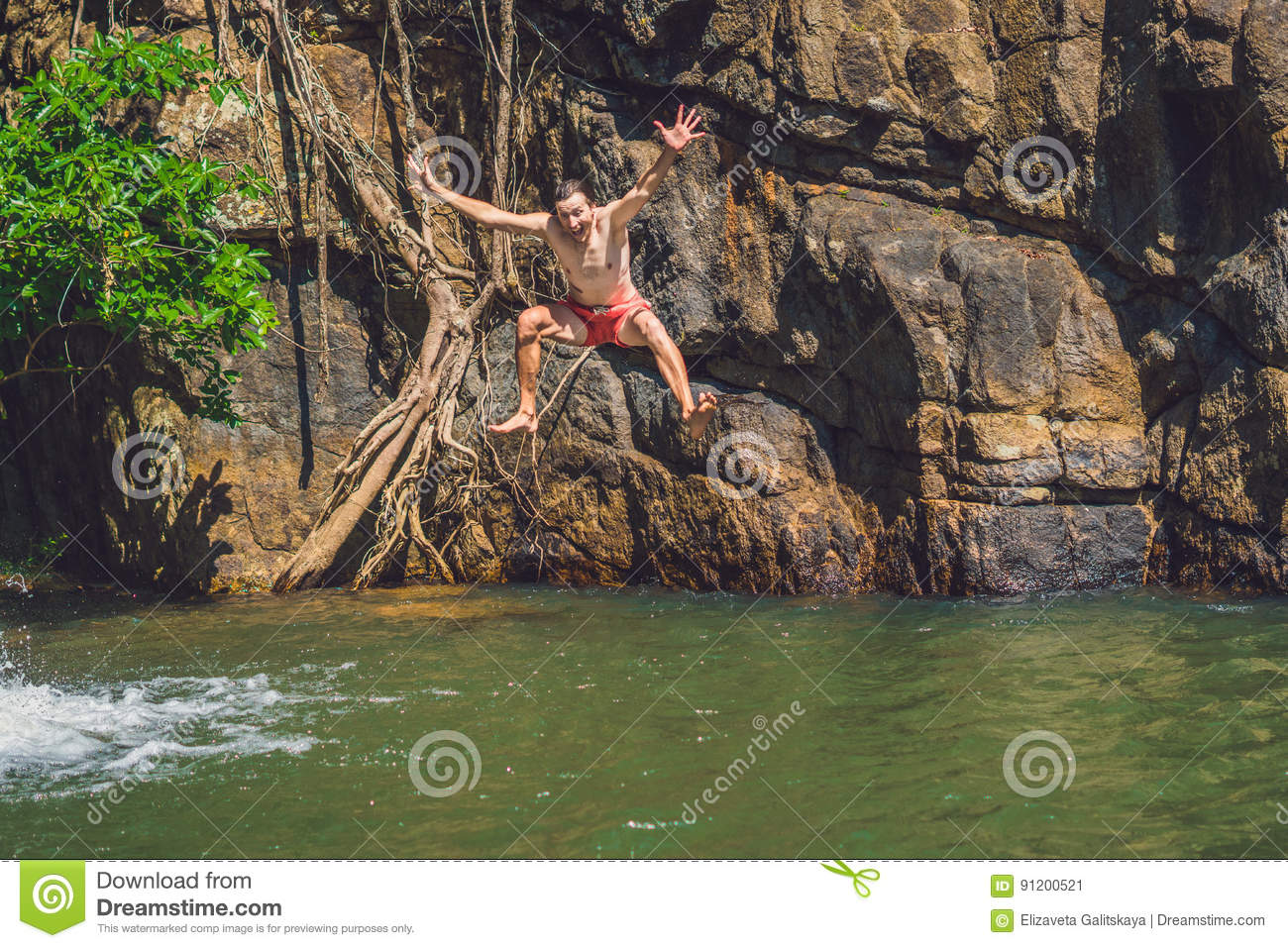 Man Jumping Off Cliff Into The Water  Summer Fun Lifestyle Stock