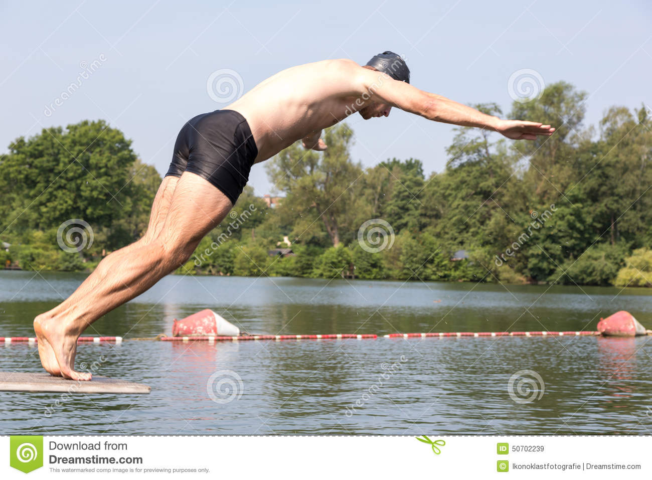 Man Jumping Off Diving Board At Swimming Pool Stock Image