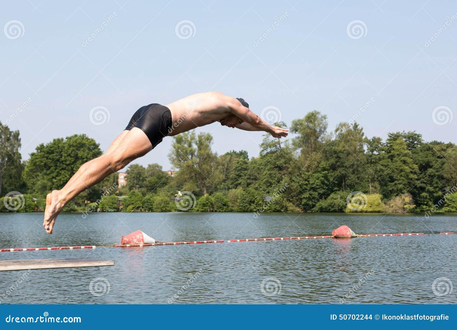 Man Jumping Off Diving Board At Swimming Pool Stock Image 50702239