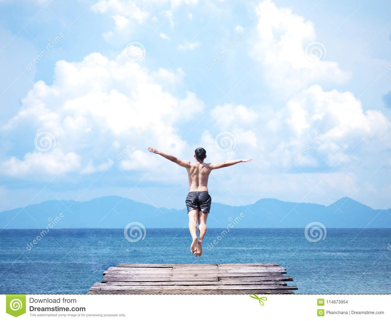 Man Jumping Off Wooden Bridge Into Blue Sea  Stock Photo - Image of