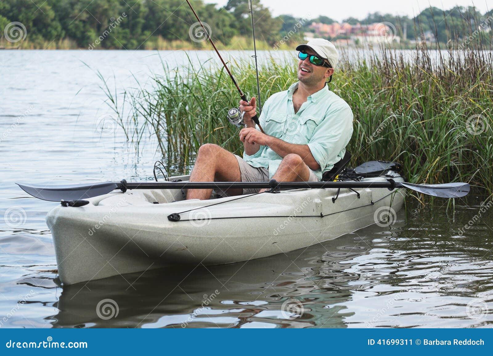 Man Kayak Fishing in Grassy Shallow Water