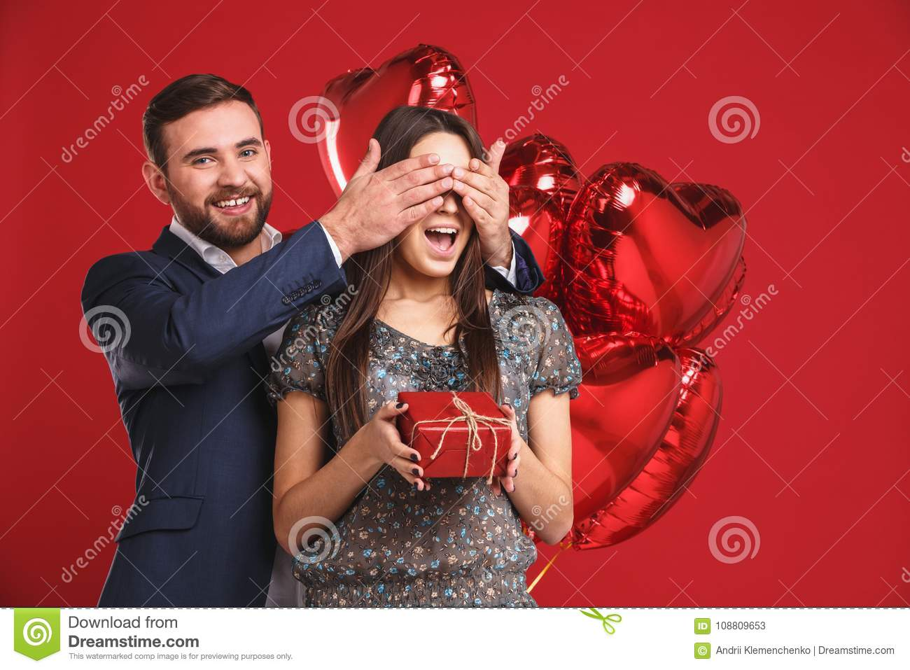 Man keeps his girlfriend eyes covered while she giving a gift , romantic surprise for Valentines day