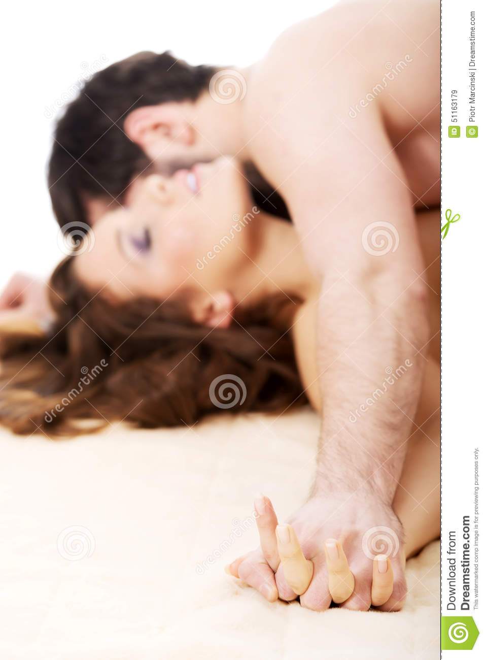 A woman and a man kissing in bed