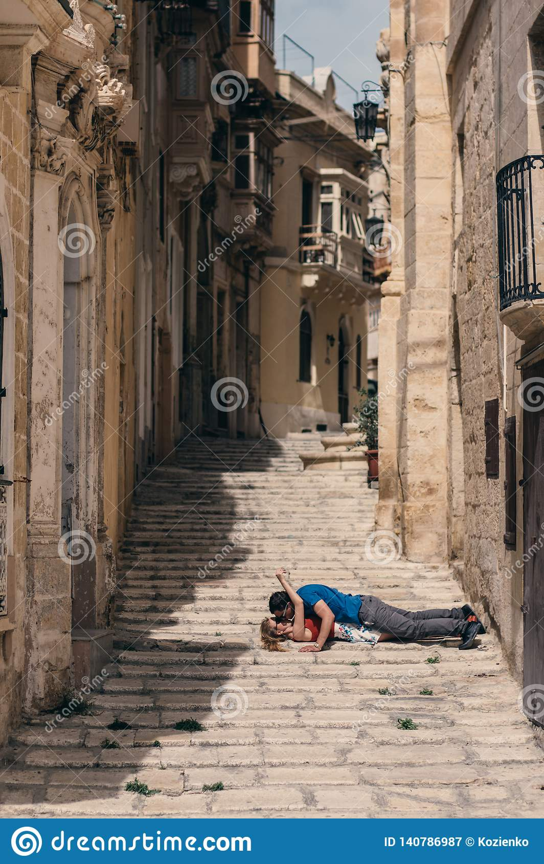 Man Kissing Woman Laying On The Stairs On The Street Stock