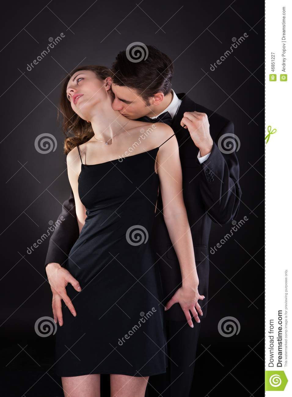 man kissing woman on neck while removing dress strap stock