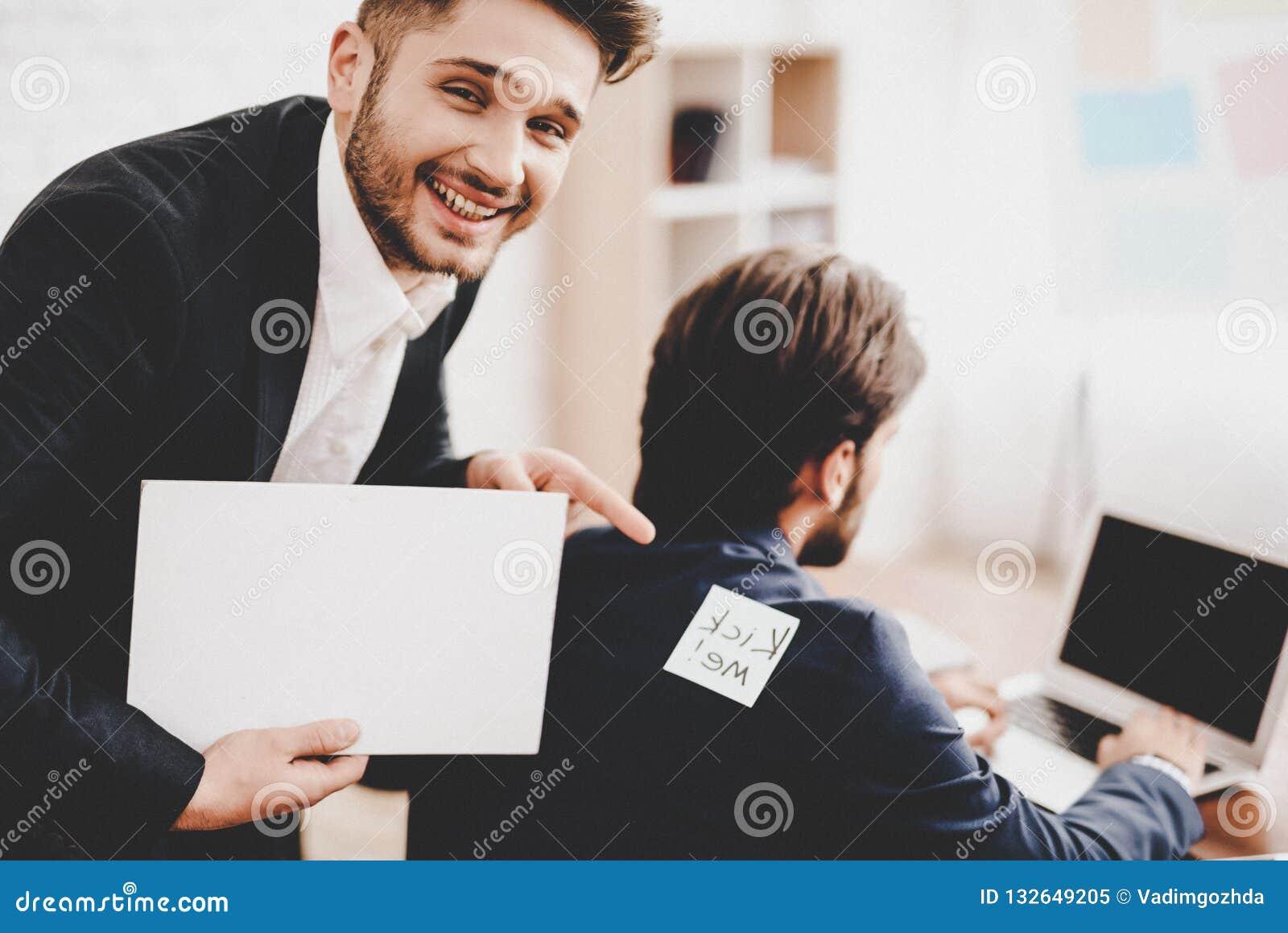 Man klistrad klistermärke på baksida av kollegan i regeringsställning
