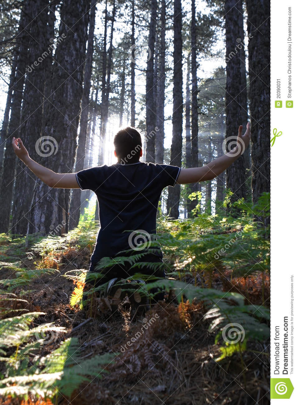 Man Kneeling with Arms Lifted in Forest