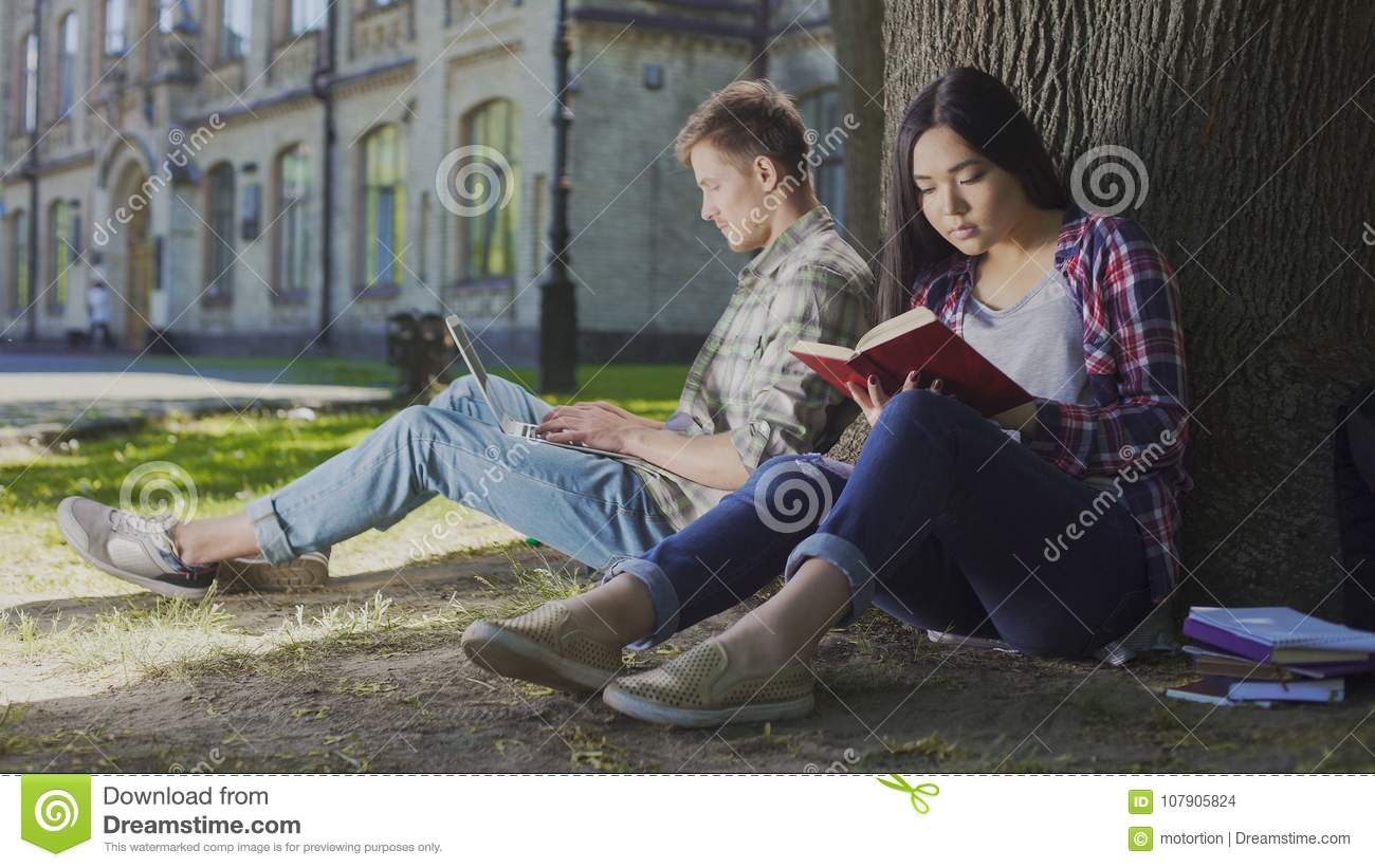 Man with laptop sitting under tree near girl reading book, contemporary youth