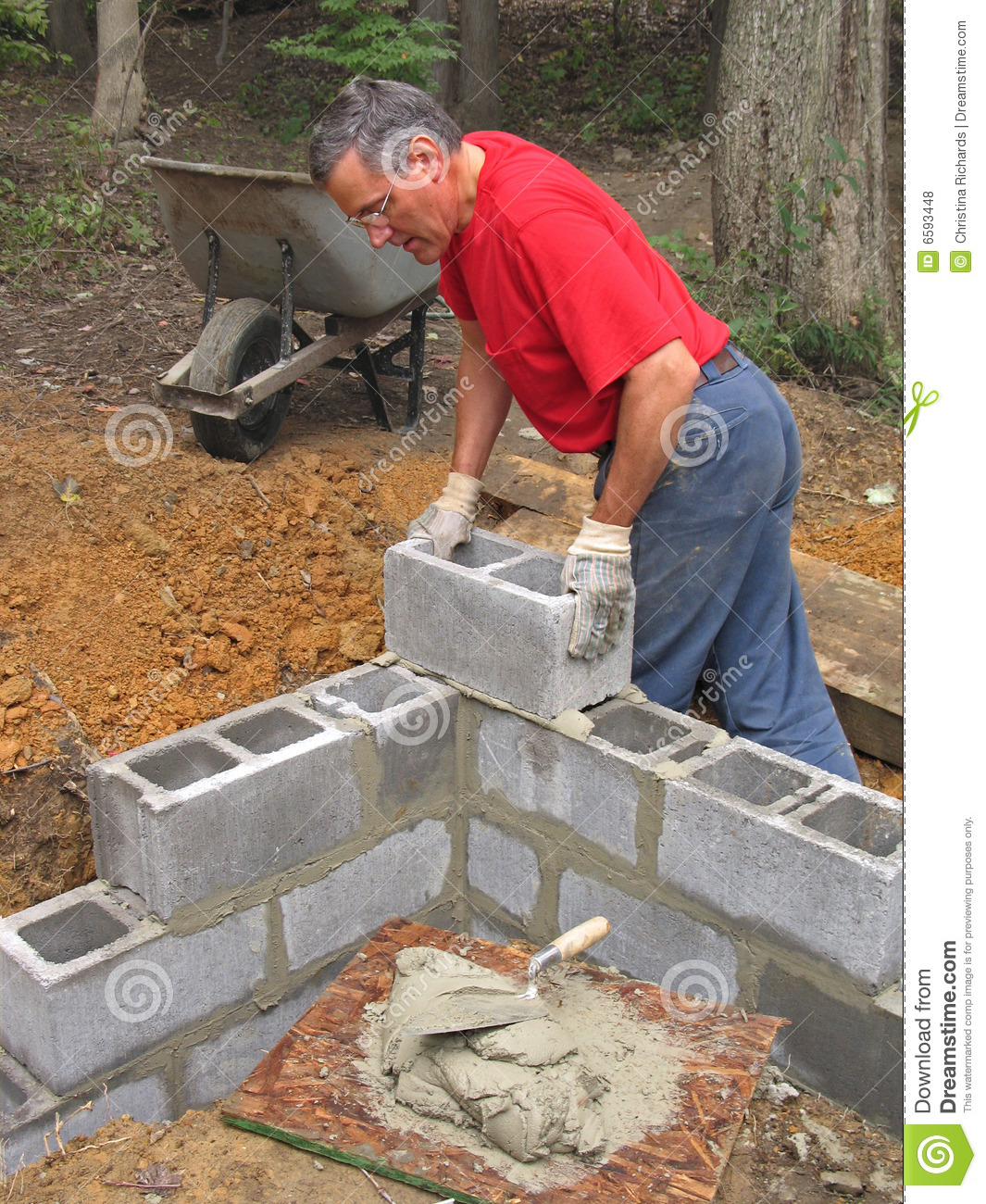 Man laying concrete block wall stock photo image of for How to build a concrete block wall foundation