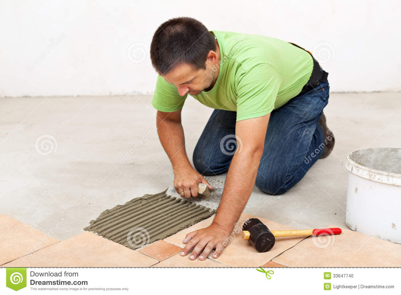 Man Laying Floor Tiles Spreading The Adhesive Stock