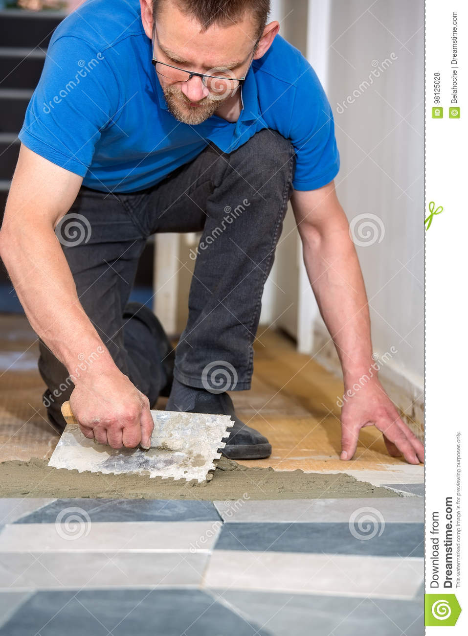 Floor tile trowel choice image tile flooring design ideas man laying floor tiles with tiling trowel stock photo image royalty free stock photo download man dailygadgetfo Gallery