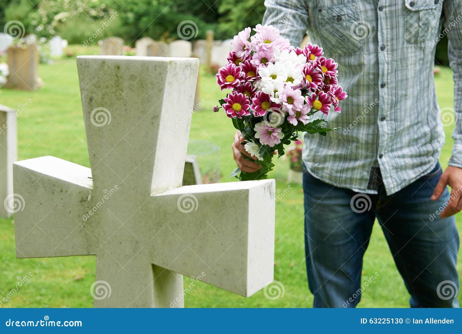 Man laying flowers on grave stock photo image 63225130 for Bouquet de fleurs homme