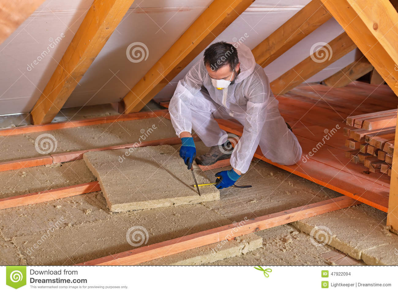 Man Laying Thermal Insulation Layer Cutting The Panels