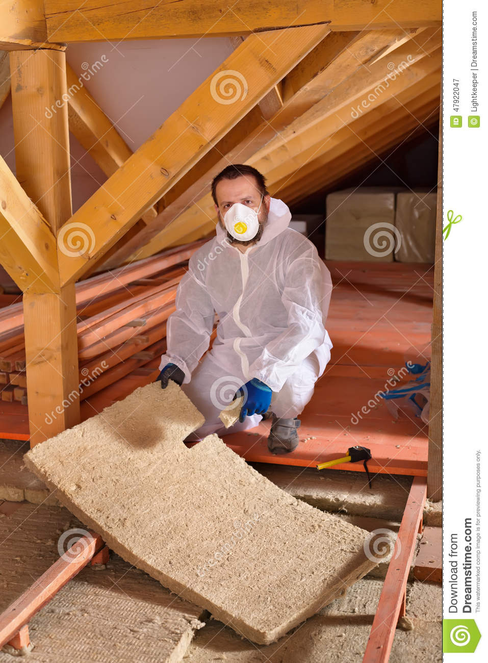 Man laying thermal insulation layer stock photo image for Mineral wool installation