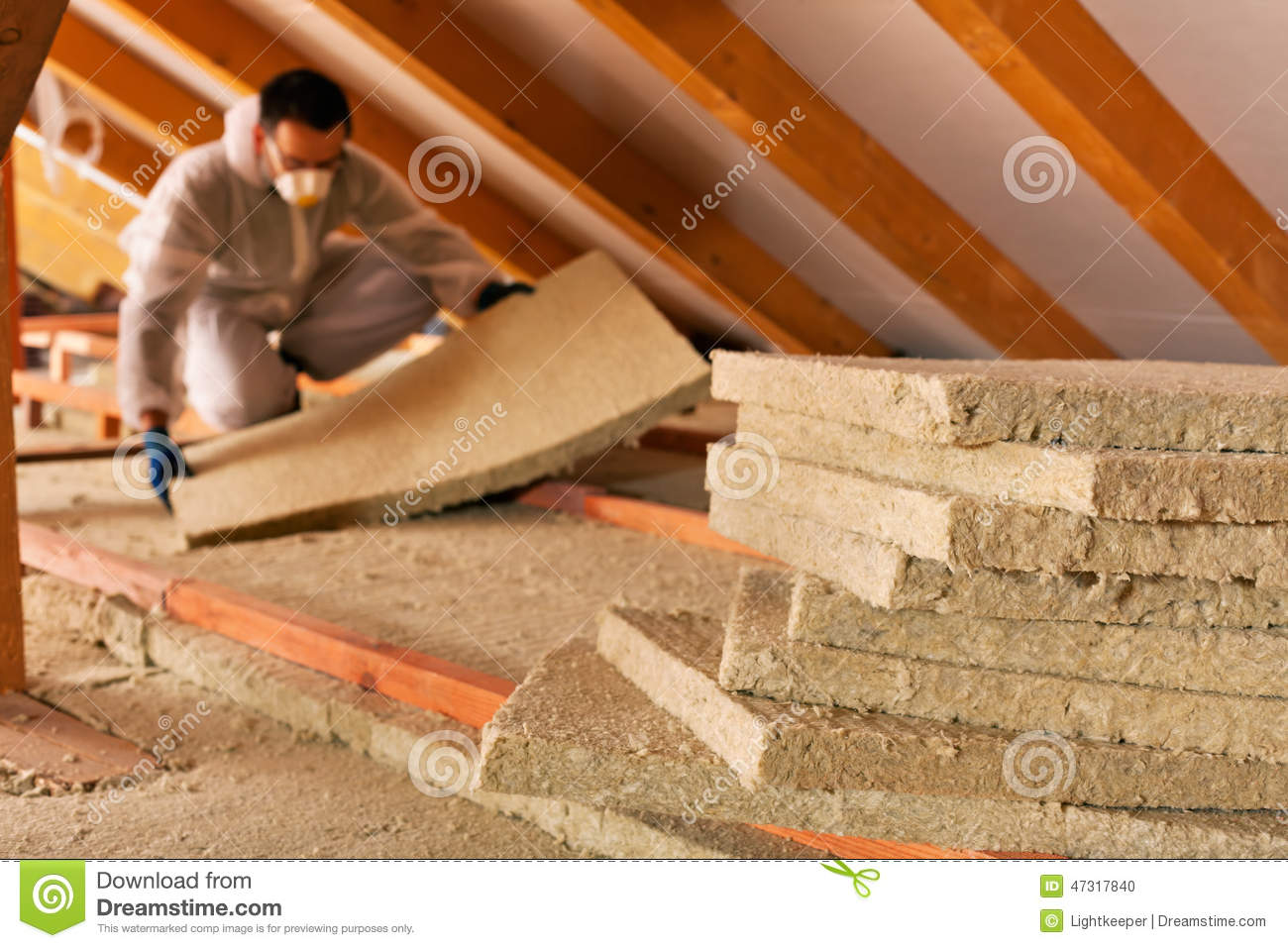 Man Laying Thermal Insulation Layer Under The Roof Stock