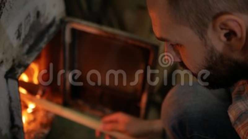 A man lights a wooden stick from the stove.  stock footage