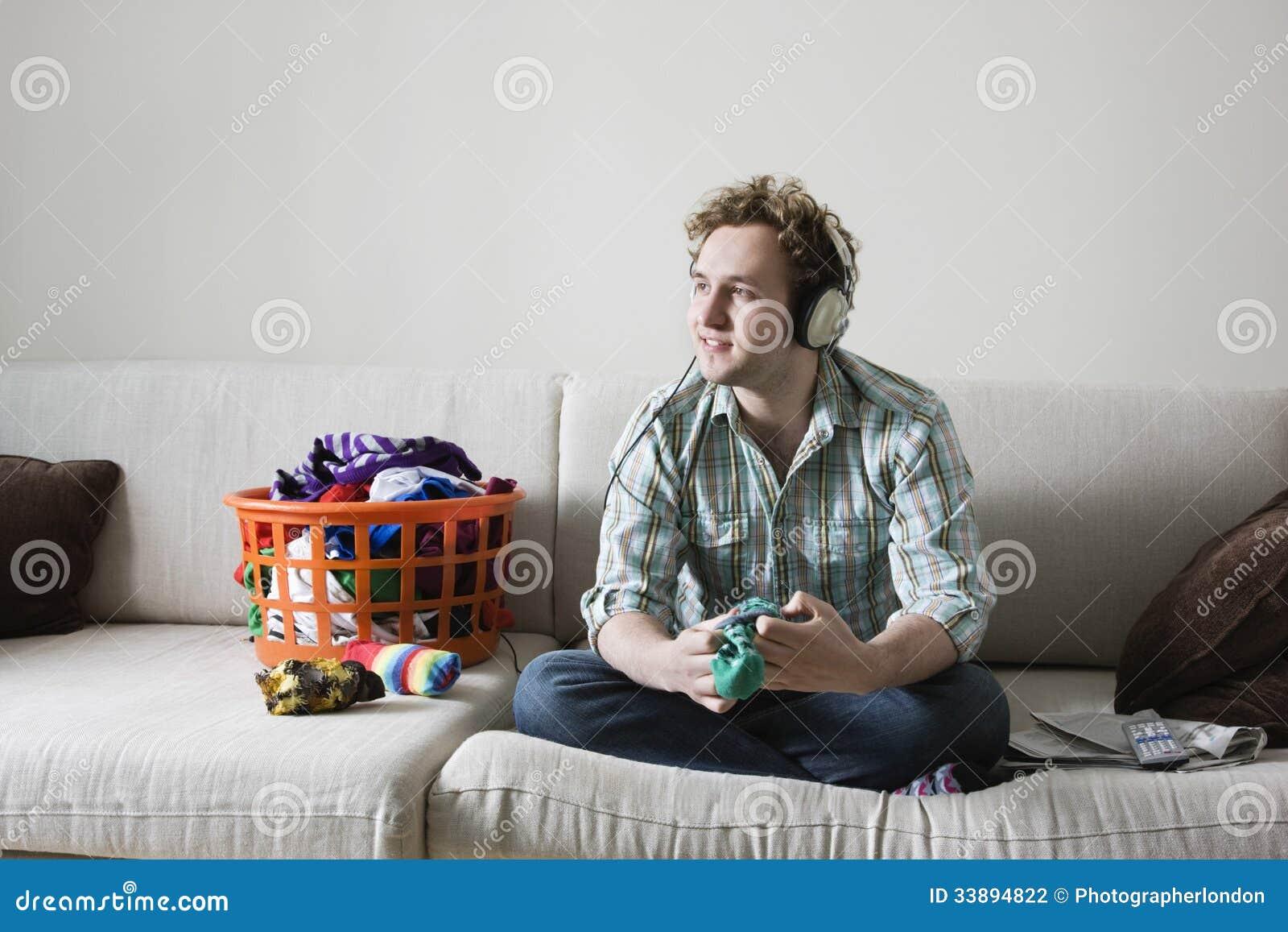 Man Listening Music While Folding Laundry On Sofa Stock