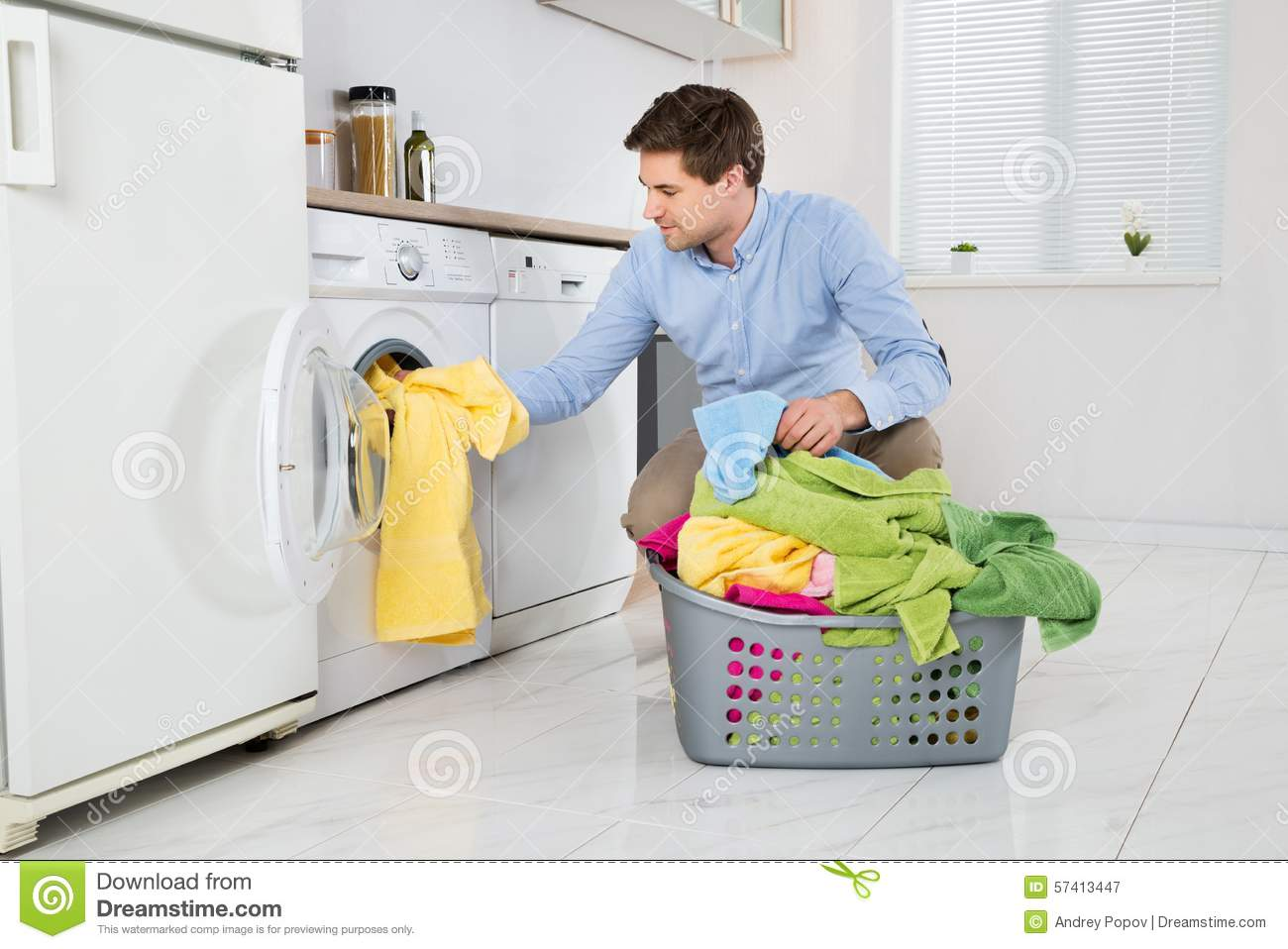 Man Loading Clothes Into Washing Machine Stock Photo
