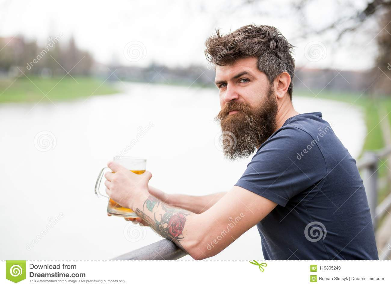 Man with long beard looks relaxed. Man with beard and mustache on calm face, river background, defocused. Bearded man