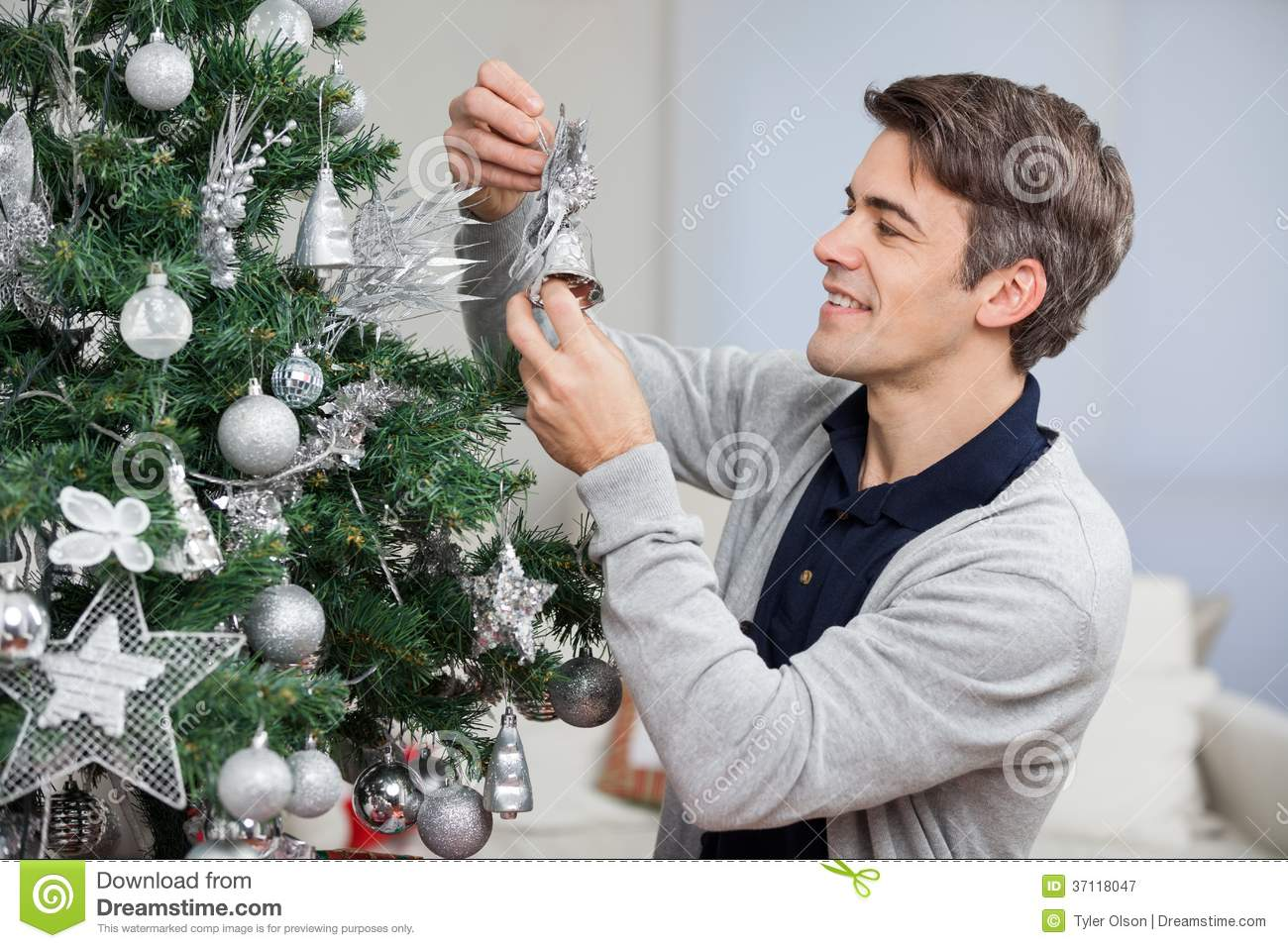 Man looking at bell while decorating christmas royalty for The power look at home decorating for men