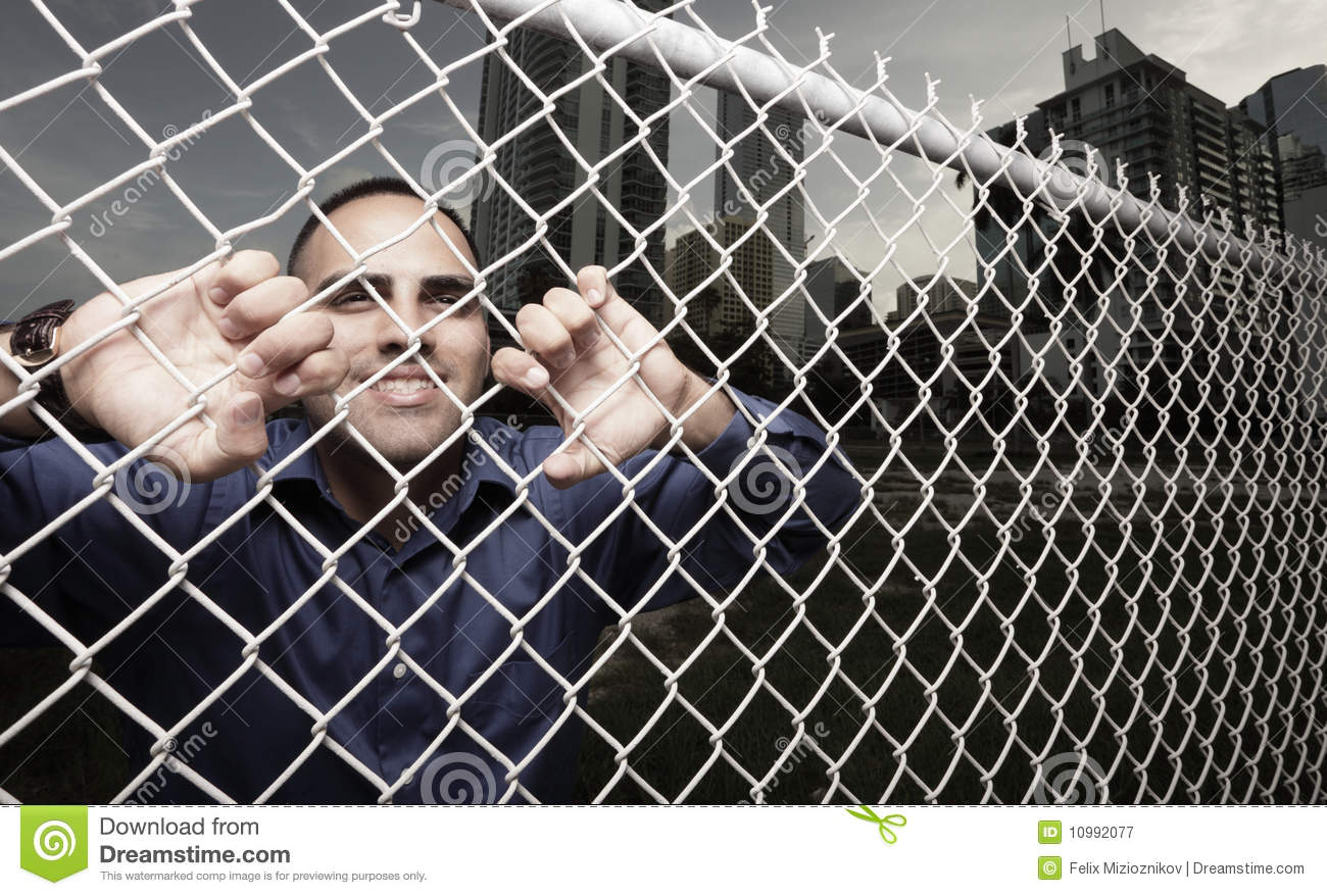 Man Looking Through The Fence Royalty Free Stock