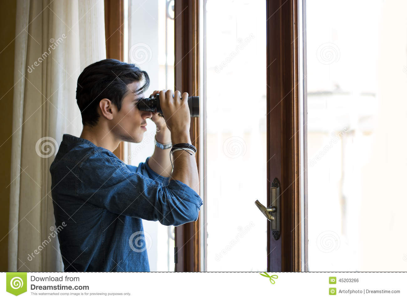 Man Looking Through A Glass Door With Binoculars Stock Photo Image