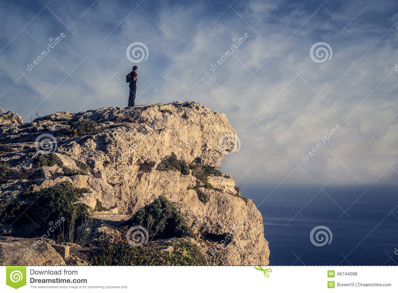 Man looking the horizon from a rock