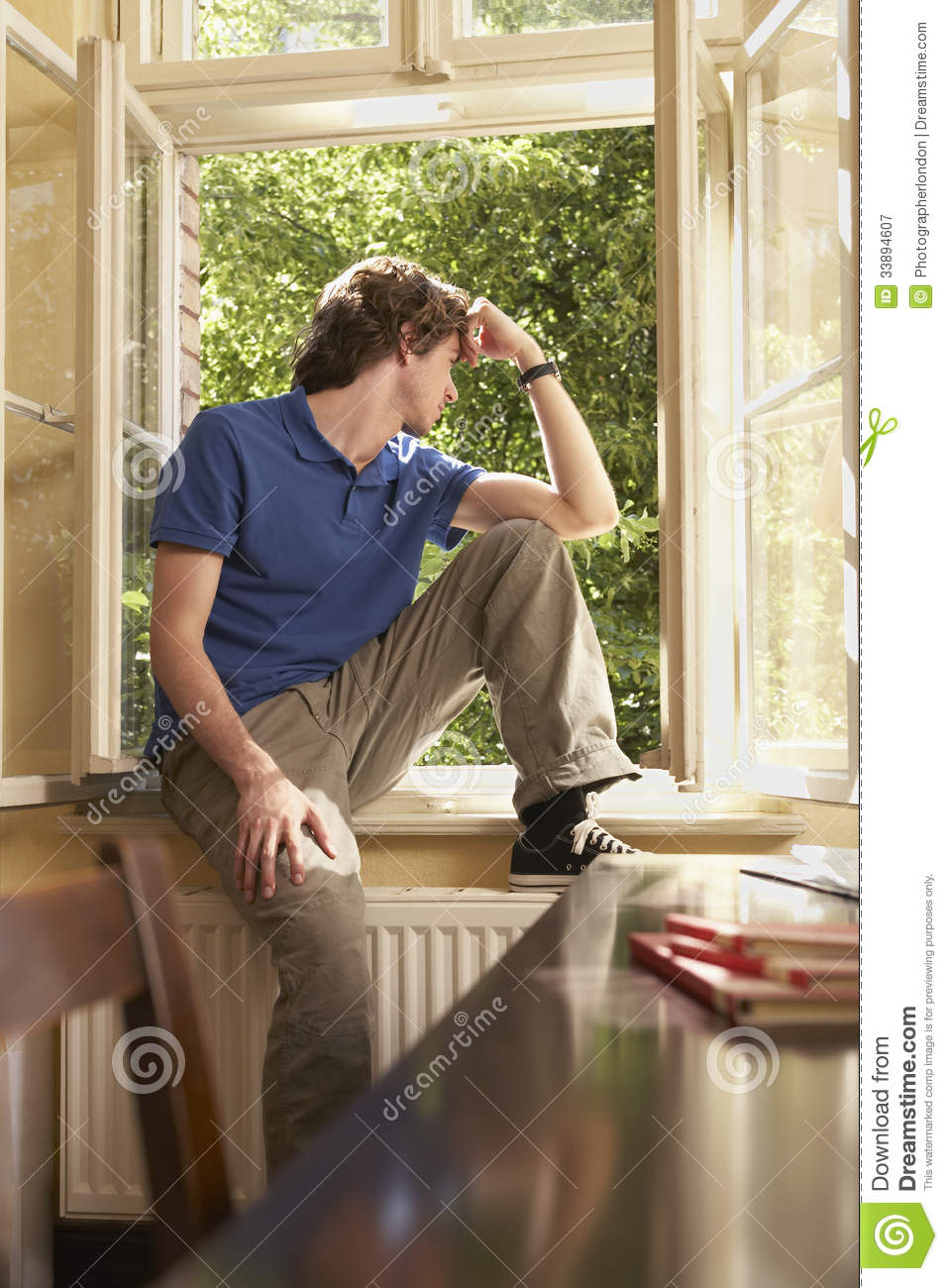 Man Looking Out Of Window Sill In Study Room Stock Image