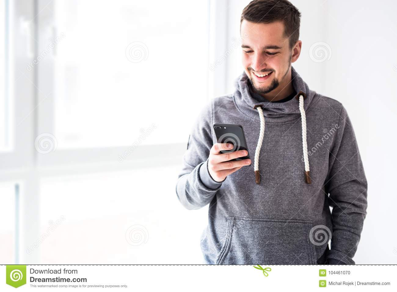 Man using smartphone in home interior