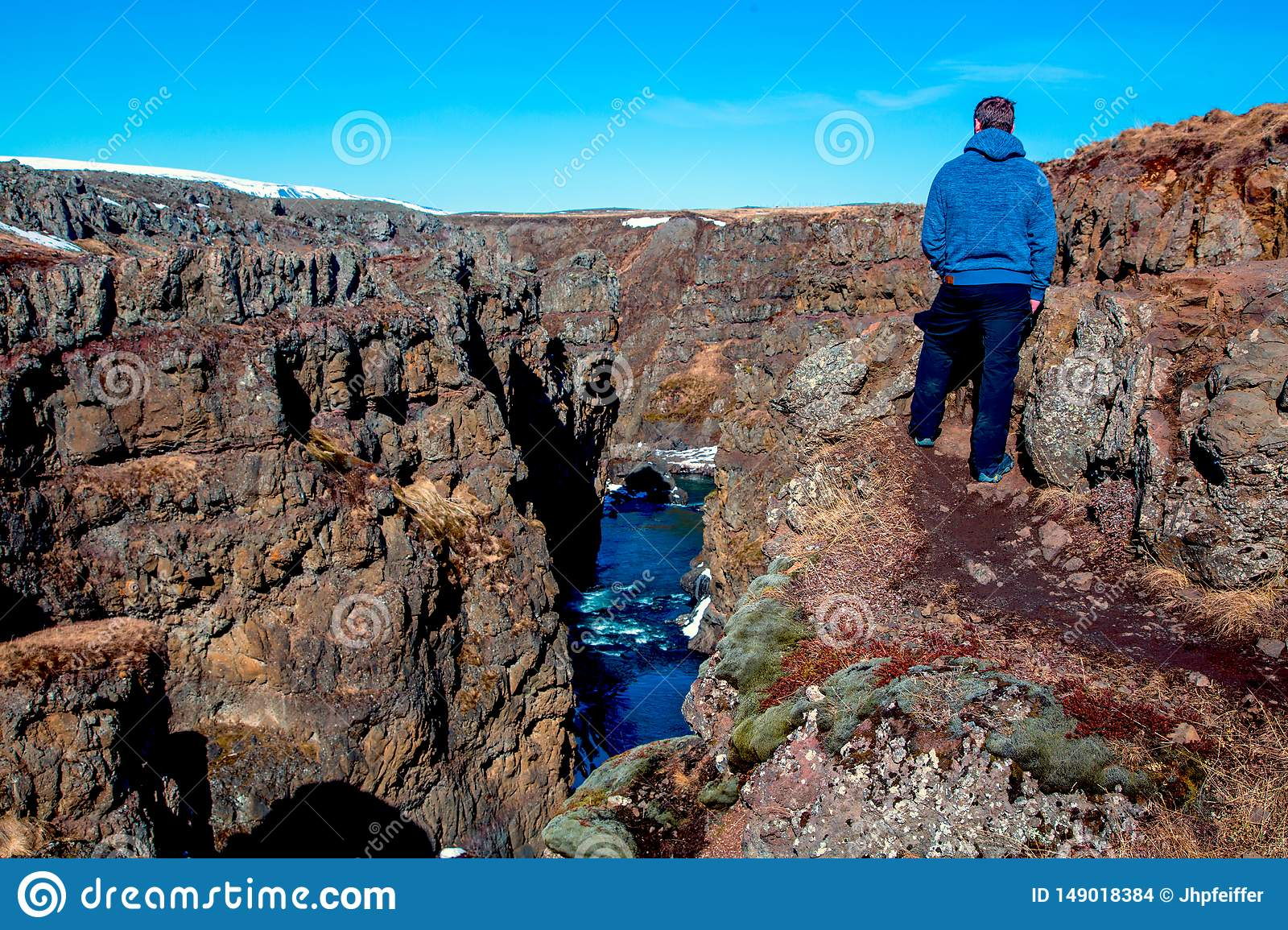 Man looks at a gorge causing a river to flow