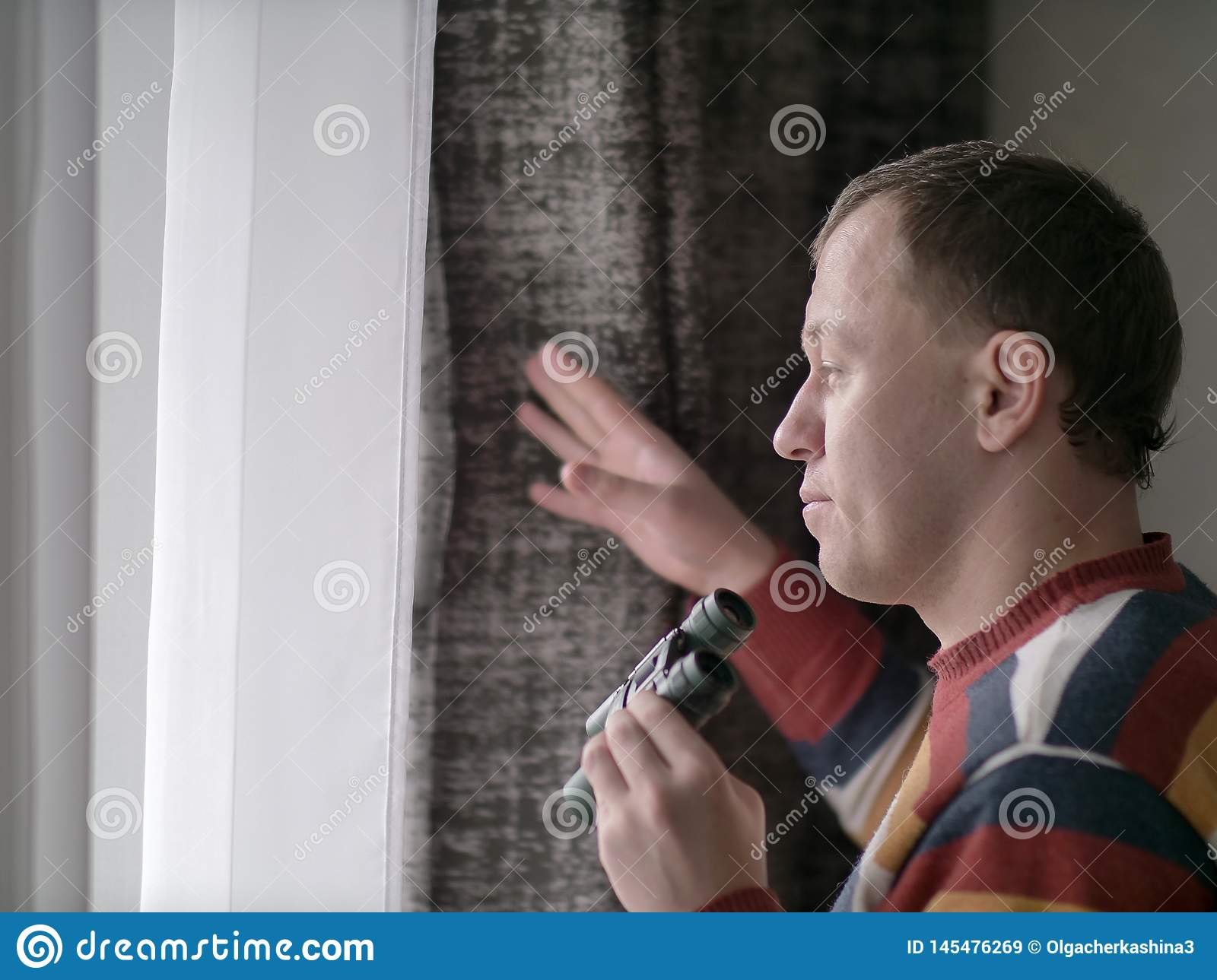 Young man looks out the window with binoculars, close-up