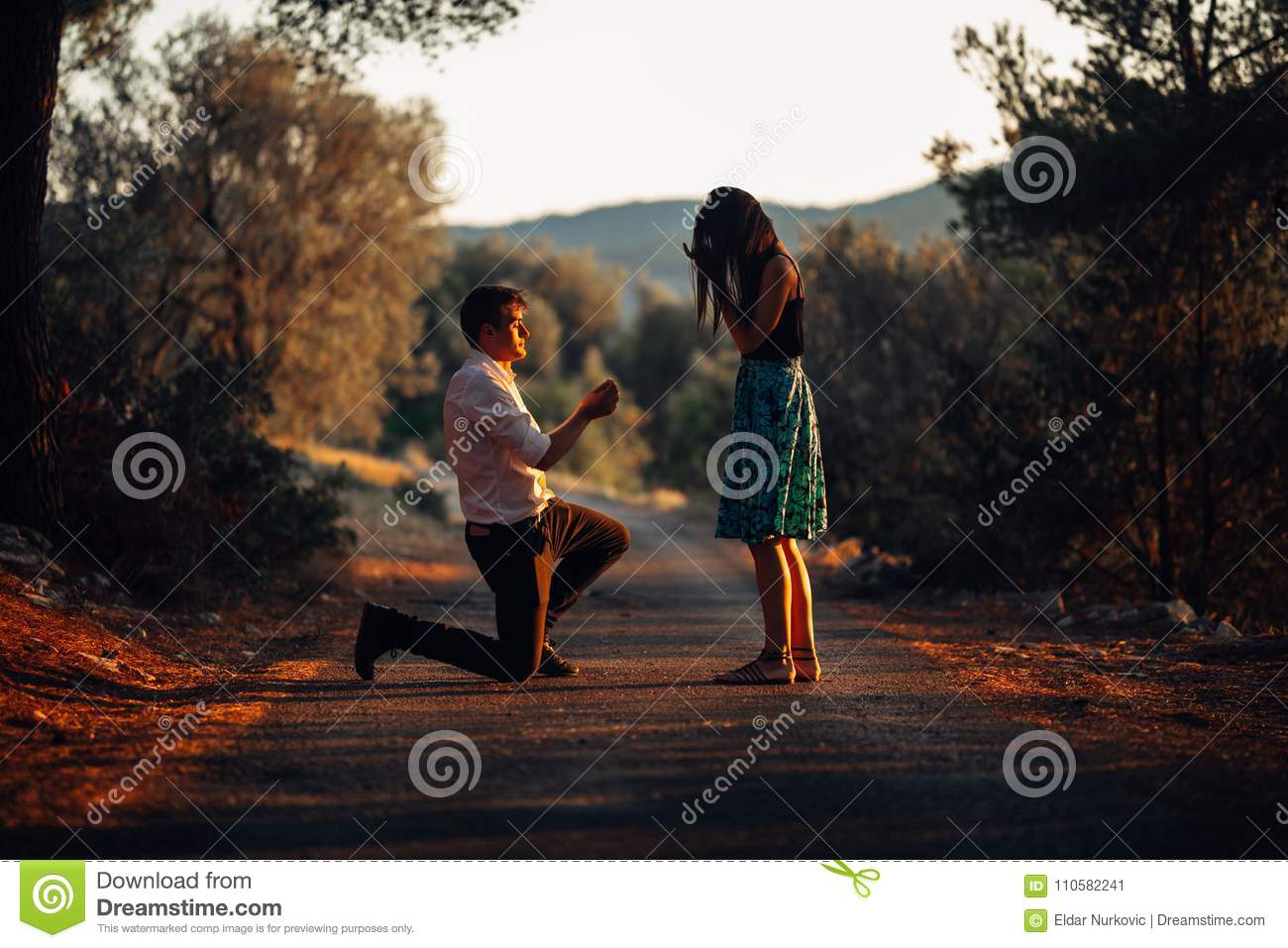 Man in love proposing a surprised,shocked woman to marry him at sunset.Proposal, engagement and wedding concept.Betrothal