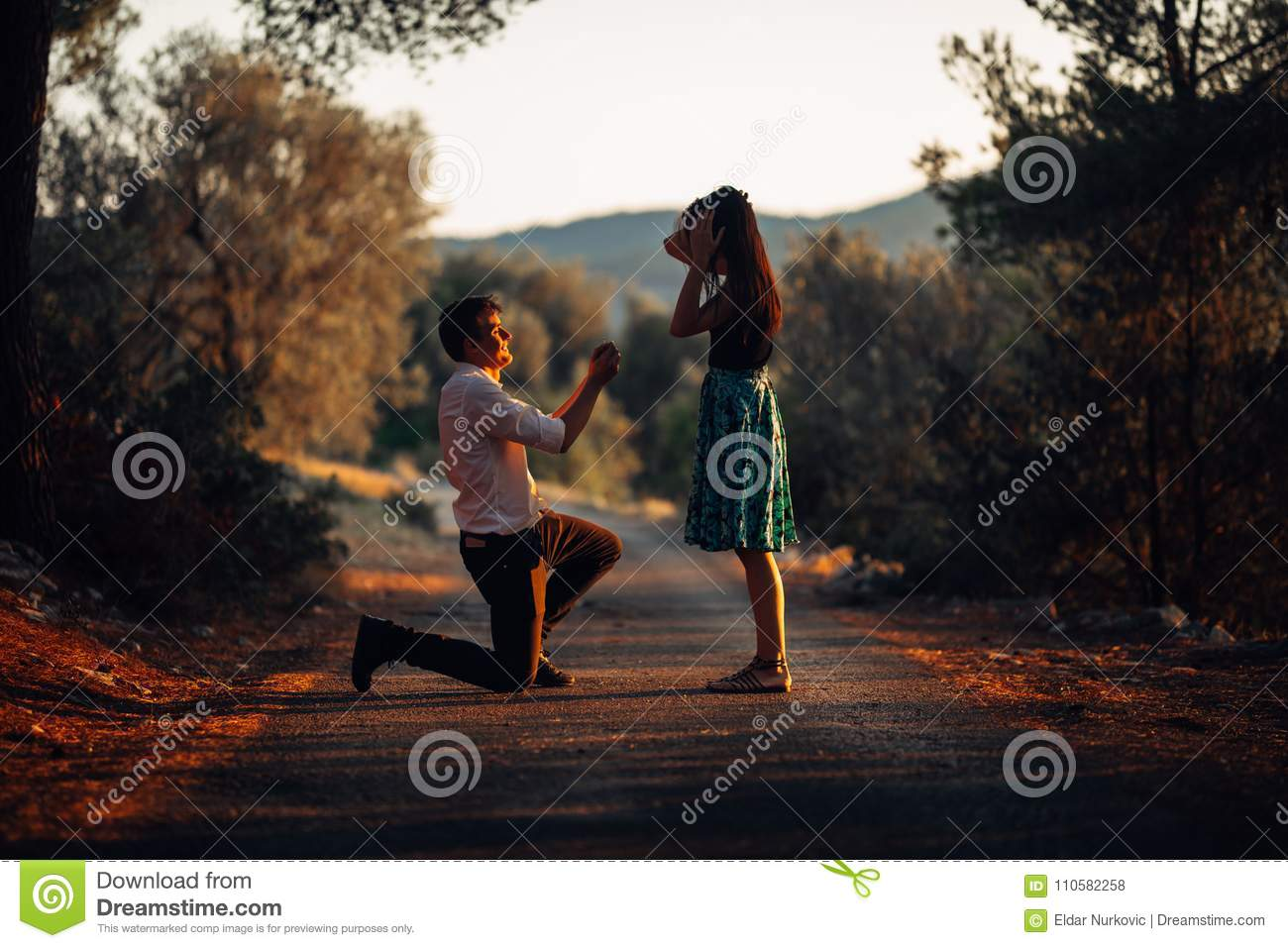 Man in love proposing a surprised, shocked woman to marry him at sunset. Proposal, engagement and wedding concept. Betrothal