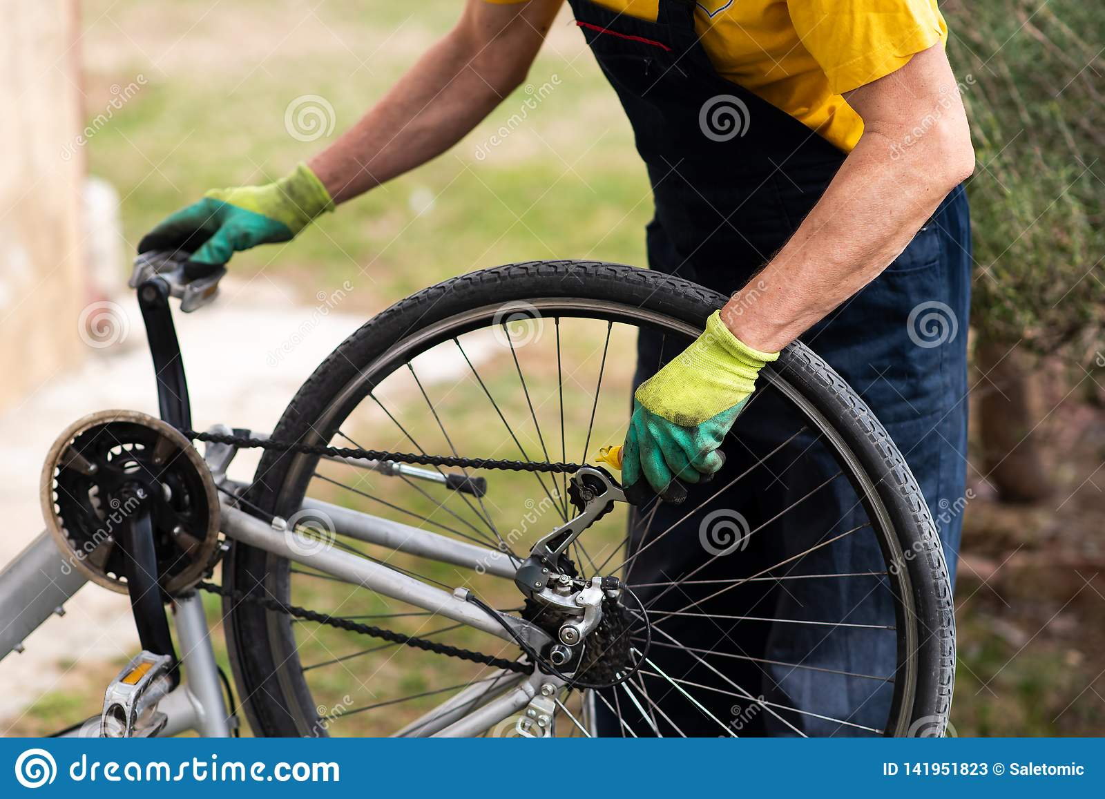 Man lubricating bicycle chain maintaining for the new season