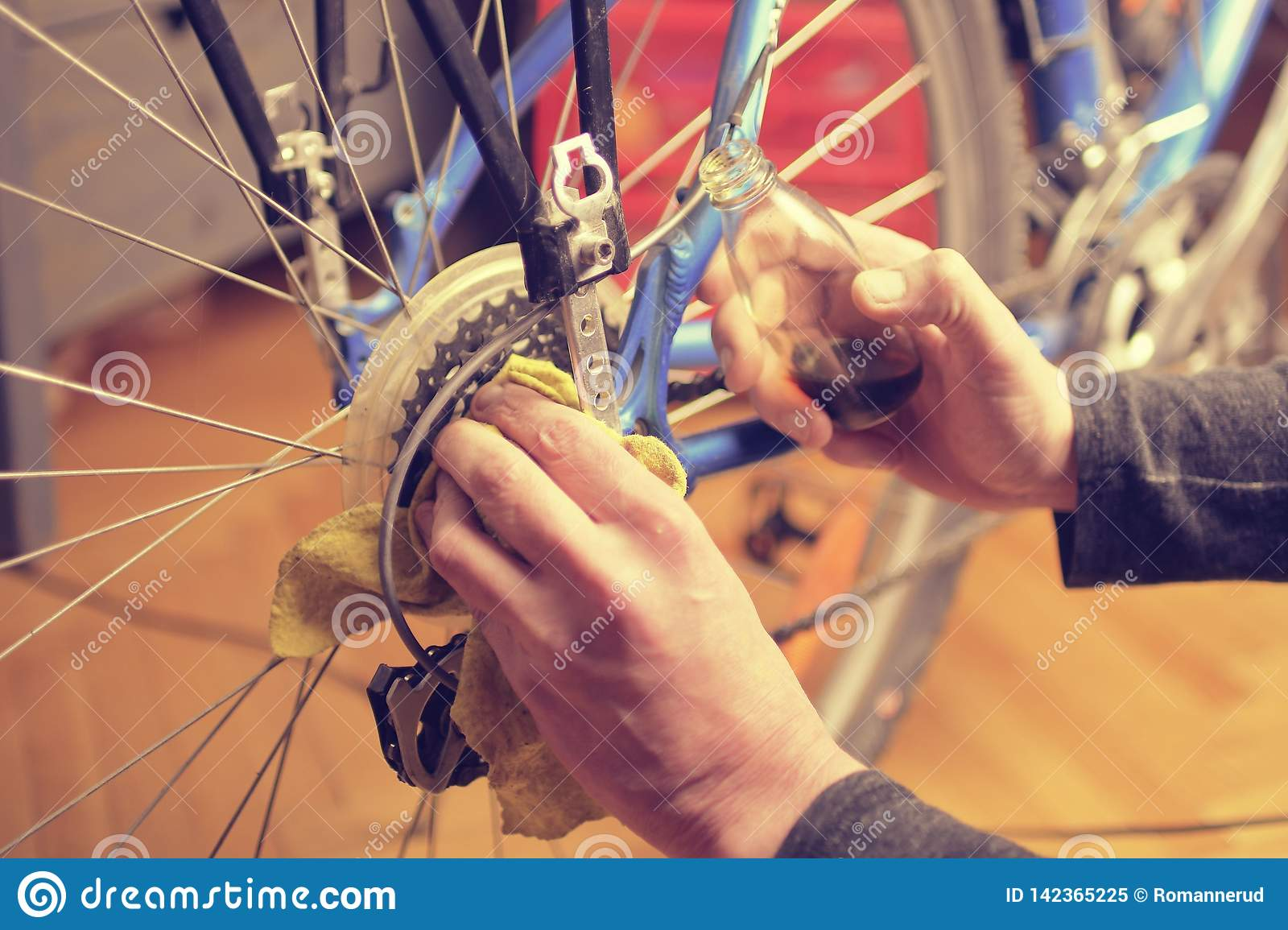 Man lubricating bicycle chain and maintaining for the new season. Oiling and repairing of bicycle drive
