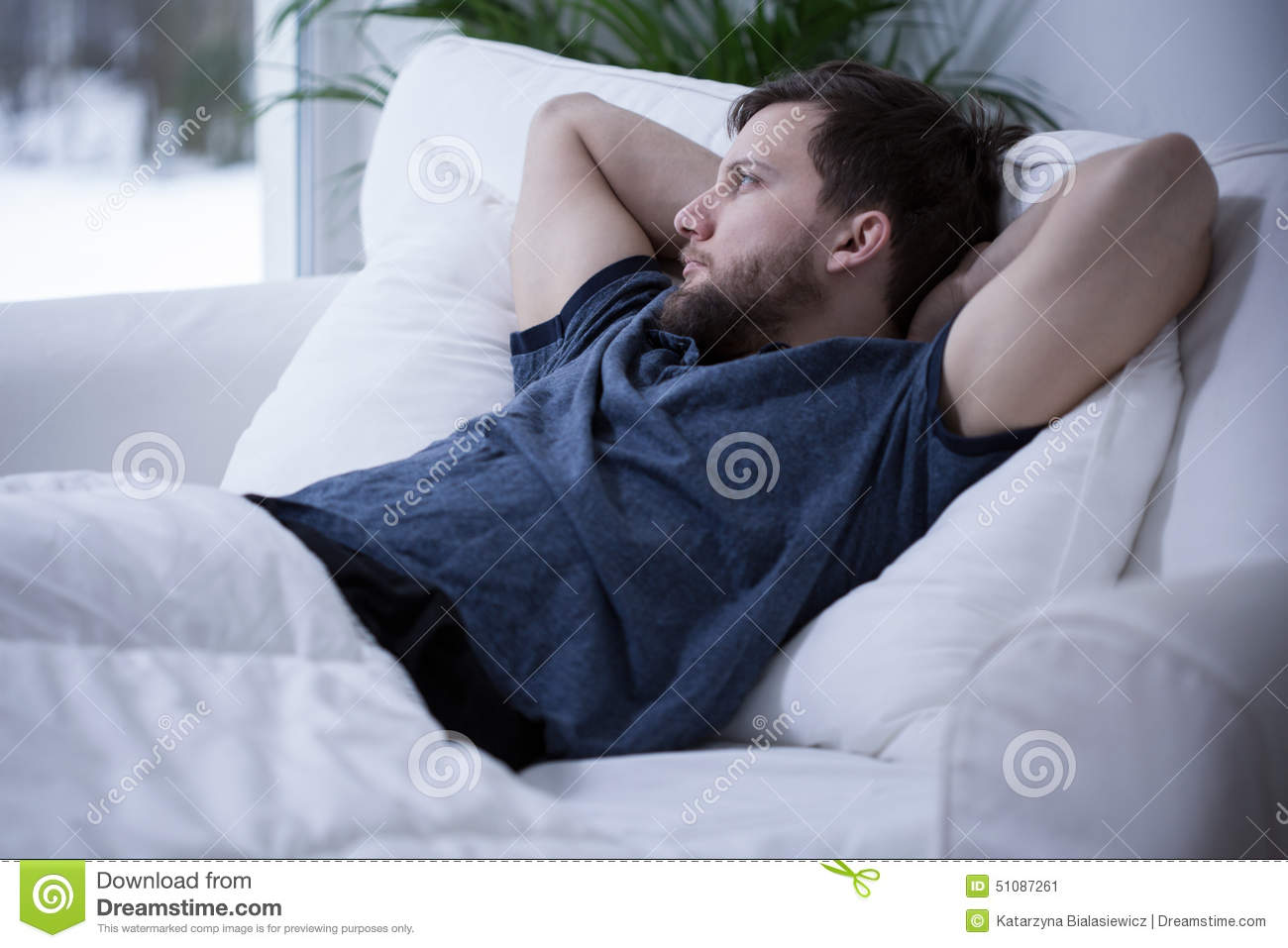 Man Lying In Bed Stock Photo